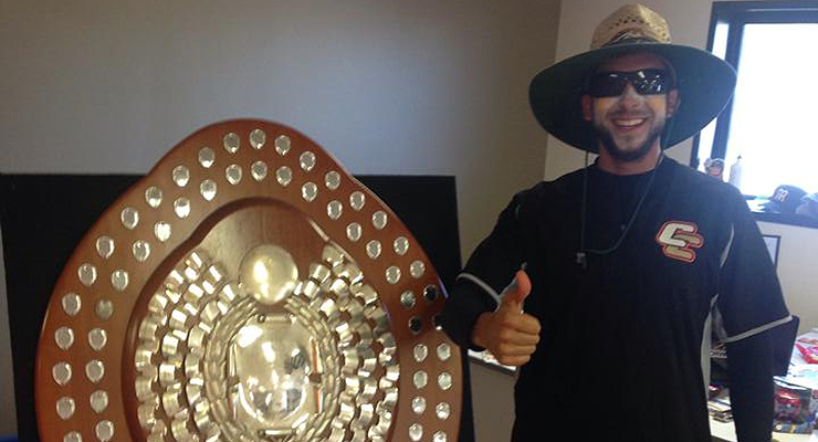A member of the Canberra Cavalry poses with the coveted Claxton Shield (via Daniel Amodio).