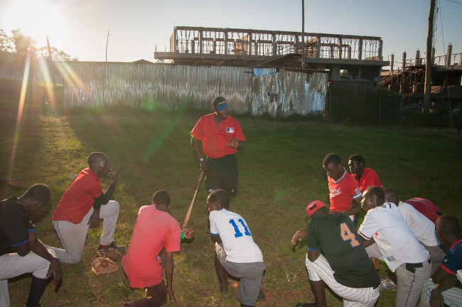 Coach George Mukhobe with a group of outfielders during practice on St. Peters Nsambya Secondary School field.